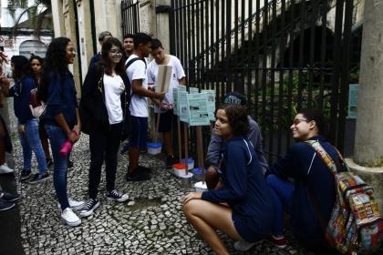 Estudantes estão parados em frente ao Outeiro de Santa Catarina e se preparam para deixar placa referencial. #Pracegover