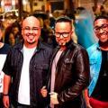 Os quatro músicos do grupo posam para a foto sorrindo, com pessoas ao fundo. #pracegover