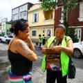 agente aborda mulher na rua com prancheta #pracegover