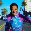 A paratleta Vanessa Cristina de Souza segura medalha no peito e sorri para foto. #Paratodosverem