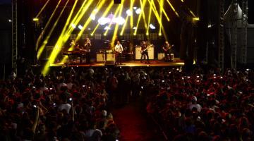 Vista geral de frente para o palco, com o público assistindo à apresentação e o grupo musical sob forte iluminação