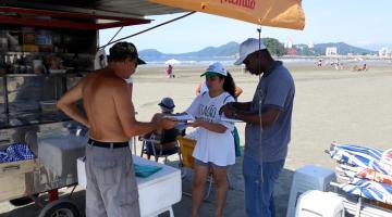 Ambulante na praia é orientado por estagiários sobre descarte de recicláveis. O homem está à frente de seu carrinho de lanche e sob um toldo. Os estagiários usam bonés de identificação. #Pracegover