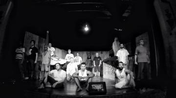 Atores da peça Barrela estão o palco. O ambiente está escuro. Há apenas uma lâmpada acesa no alto. #Pracegover