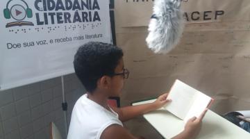 menino lê livro e há um microfone acima dele para gravação #pracegover