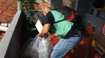 Agente revolve plástico em residência para verificar se há presença de larva de mosquito. #Pracegover