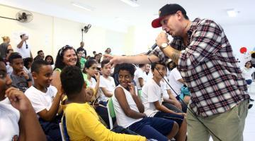 Rapper interagem com crianças e adolescentes na plateia. #Pracegover