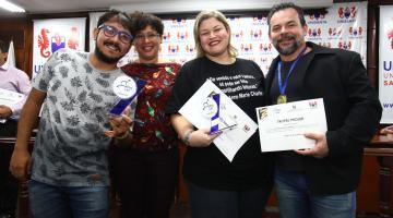 professores premiados mostram trofeus e certificados #pracegover