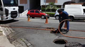 Funcionário insere mangueira em poço de visita para execução da limpeza da rede de dreangem. O trecho onde ele trabalha está sinalizado por três cones. Há veículos na rua. #Pracegover
