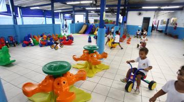 Pátio da escola com brinquedos infantis coloridos. Algumas crianças andam em triciclos. #Pracegover