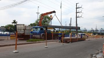 caminhão com guindaste ergue peça da construção #pracegover