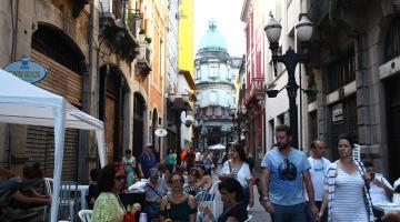 Turistas caminham por rua do centro durante o festival #pracegover