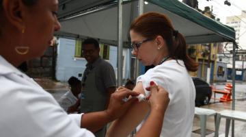 Mulher é vacinada por outra sob tenda na rua. #Pracegover