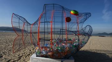 Peixe na praia com lixo dentro #pracegover