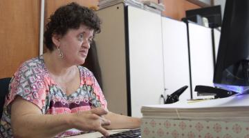 Gesilene está sentada à mesa de trabalho e usa o teclado do desktop