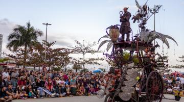 Apresentação artística no emissário. Homem está no alto de um grande triciclo cheio de parafernália. #Pracegover