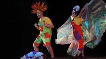 Três atores fantasiados fazem performance no palco #pracegover
