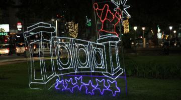 Armação decorativa de Natal, com mureta estilizada e iluminada sobre o jardim da orla. #Pracegover