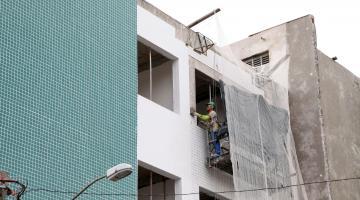 Homem está sobre andaime trabalhando no revestimento de prédio. Ele está na altura na altura do quarto e último pavimento. #Pracegover