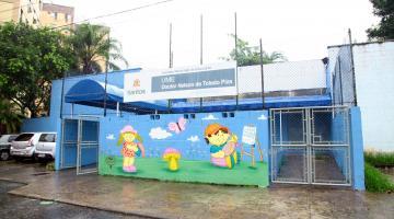 Fachada da escola Nelson de Toledo Piza, com muro pintado com motivos infantis. #Pracegover