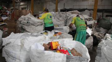 Homem e mulher separam material reciclável em sacos. #Pracegover