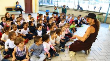 Ator vestido de palhaço fala com crianças, sentadas #pracegover