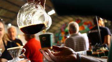 Close up de mão segurando jarra despeja café em um copo. Ambiente está cheio de pessoas. #Pracegover