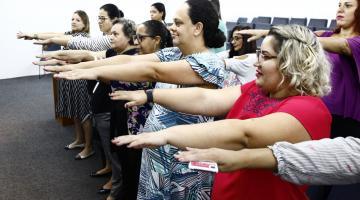 Mulheres estão lado a lado, em pé, e todas com os braços estendidos. Elas fazem exercícios coordenados. #Pracegover