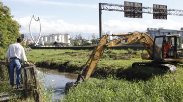 Limpeza de canal próximo à Marginal Anchieta. À direita se vê uma escavadeira revolvendo o canal. Ao fundo, o monumento O Peixe. #Pracegover
