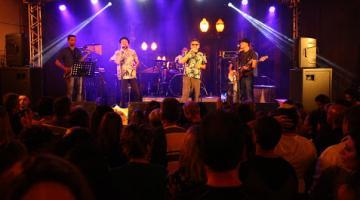 Show de Simoninha e banda Carlos Bronson. Palco está iluminado. Quatro músicos estão à frente. Público está de costas para a imagem. #Pregover
