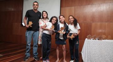 Crianças premiadas estão no palco segurando troféus. São três meninas. Atrás há um casal. #Pracegover