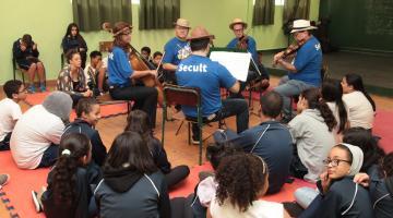 Músicos tocam com alunos sentados em volta #pracegover
