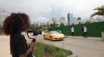 mulher grava carro amarelo para cena do clipe #pracegover