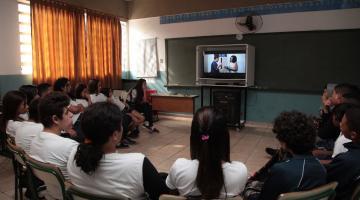Crianças estão em círculo assistindo ao filme #pracegover