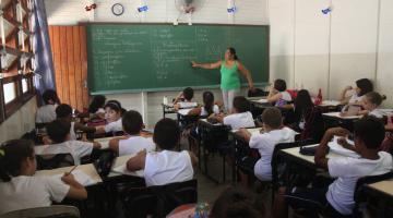 Alunos em sala de aula. Professora está ao fundo diante da lousa para a qual aponta com a mão direita. #Pracegover