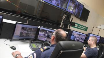 Central de monitoramento com vários telões afixados em parede e outros sobre uma grande bancada. Dois homens uniformizados da Guarda Municipal operam aparelhos. #Pracegover