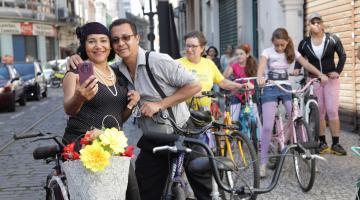 Casal em cima de bicicletas se abraça e faz selfie #pracegover