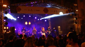 Músicos estão no palco iluminado e público está de costas para a foto. #Pracegover