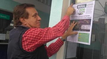 Homem fixa mural em vidro de estabelecimento. #Pracegover