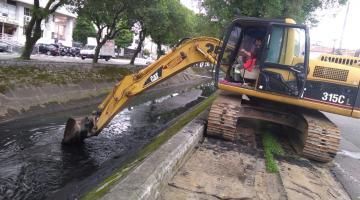Maquina com pá carregadeira retira sedimentos do fundo de canal. #Pracegover