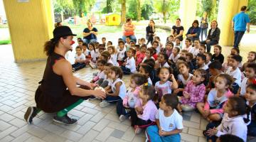 Mulher com nariz de palhaço conta histórias a crianças sentadas no chão. #Pracegover
