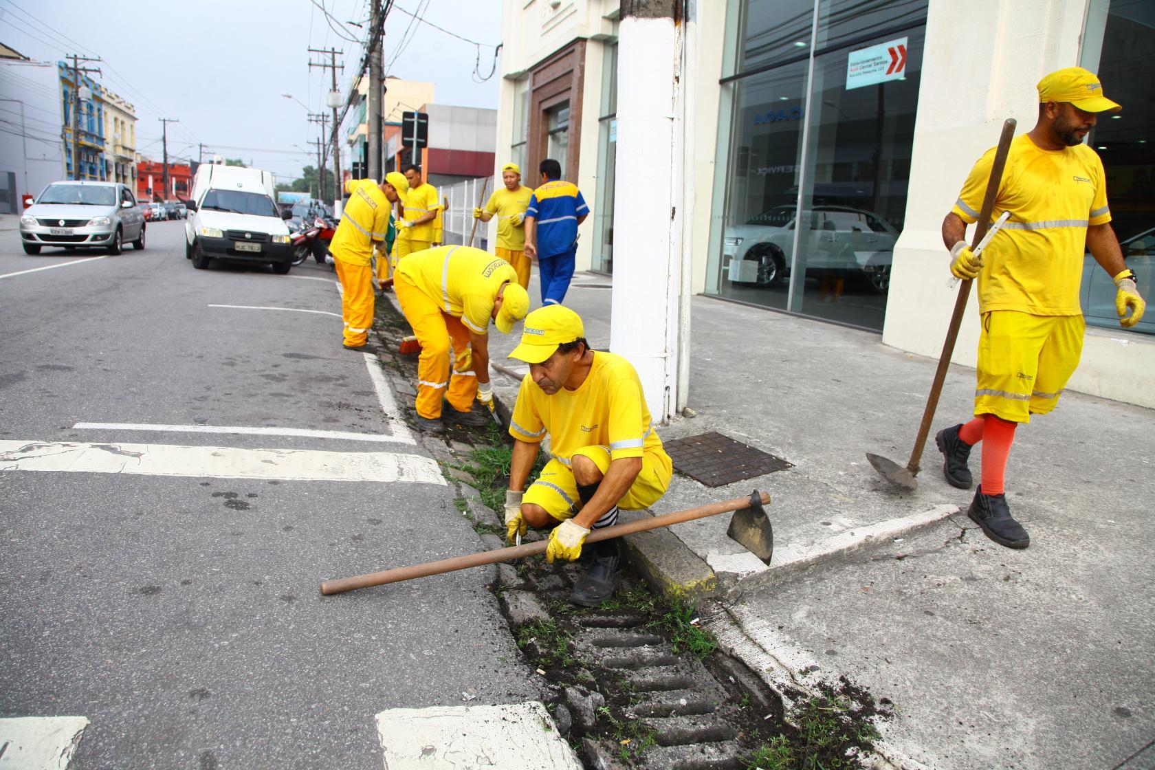 Funcionários limpam sistema de drenagem com acesso por bocas de lobo. #Pracegover