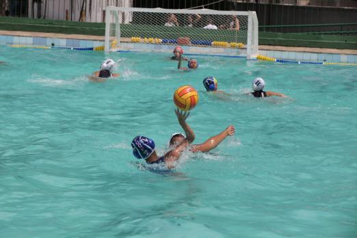 A piscina com atletas jogando polo aquático. Ao fundo está a trave. #Pracegover