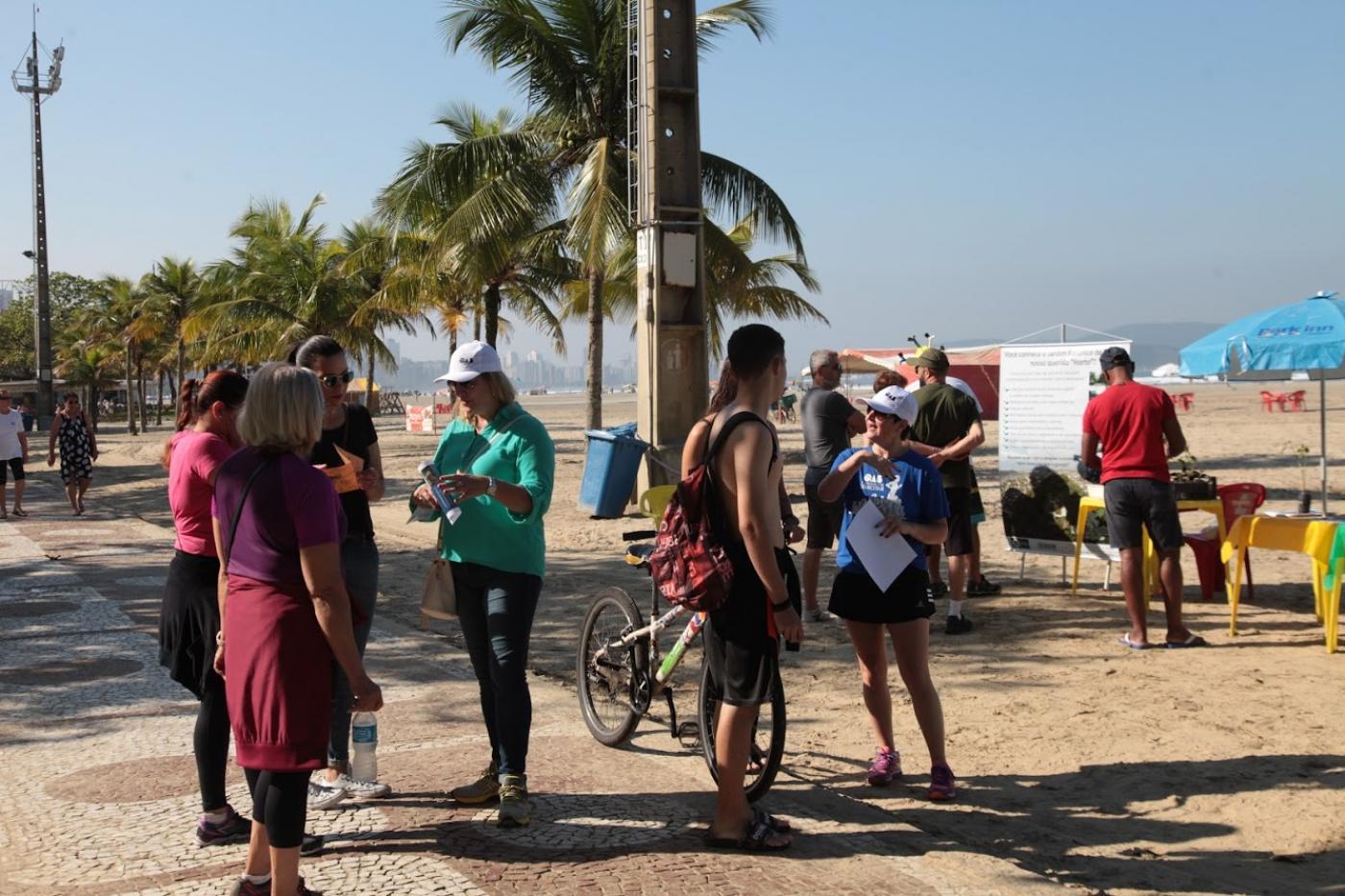 Voluntários entregam folhetos na orla. Pessoas estão no calçadão próximo à areia. #Pracegover