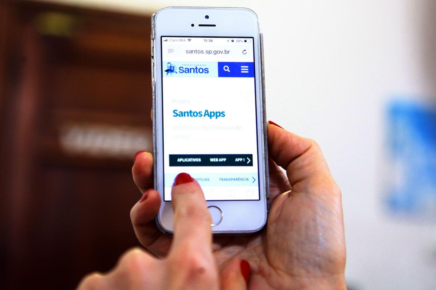 Mão direita segura smartphone enquanto mão esquerda digita em aplicativo. #Pracegover