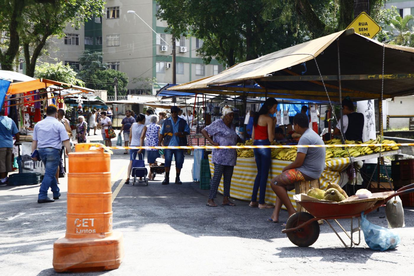 Barracas armadas em ambos os lados de uma rua. Consumidores circulam pela via. À entrada há cavalete e fita zebrada para impedir o trânsito no local. #Pracegover