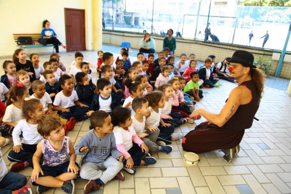 homem fextiso de palhaço fala com crianças sentadas no chão #pracegover