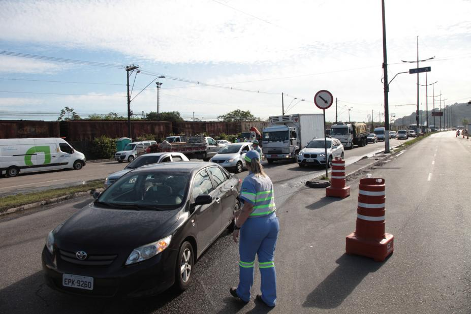 Agente monitora trânsito na entrada da Cidade.Veículos estão circulando. Há cones bloqueando acesso à pista ao lado direito da imagem. #Pracegover