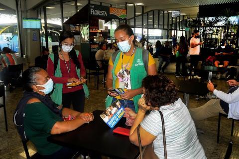 Duas agentes educativas, em pé, conversam com duas mulheres, sentadas, no Terminal Rodoviário. #pracegover