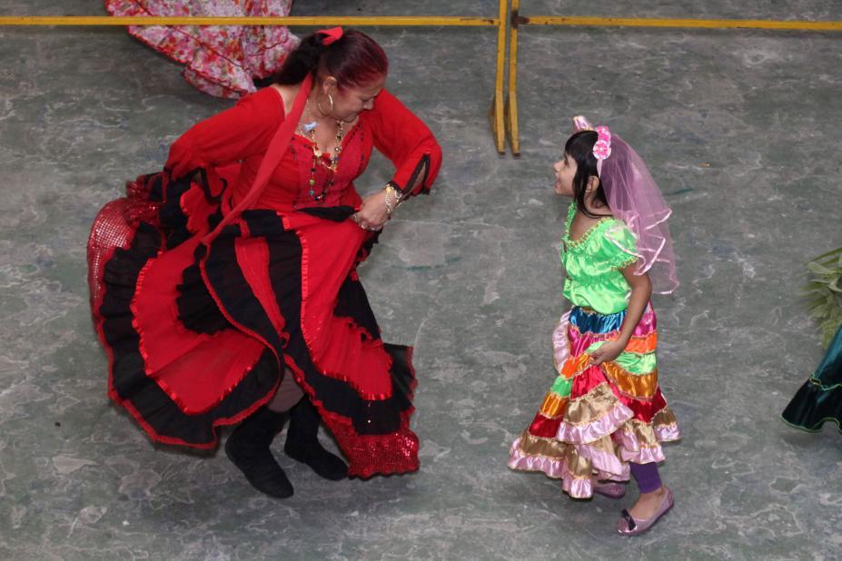 18deecc67 Mulher e menina vestidas com roupas típicas ciganas dançam em uma quadra.  Elas estão uma Festa ...