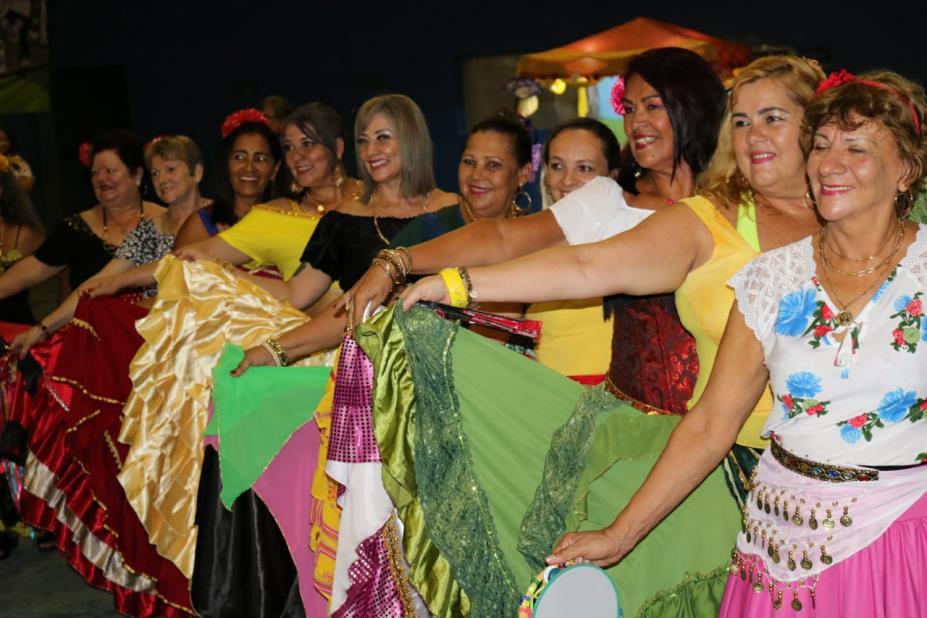 8f0830d2a Enfileirtadas, dez mulheres com trajes típicos ciganos levantam parte das  sais em pose para foto